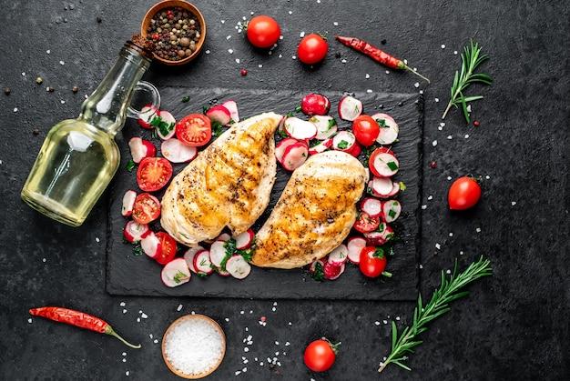 Petto di pollo alla griglia e insalata con verdure fresche pomodori e ravanelli in un piatto carne di pollo con insalata cibo sano sul tavolo di pietra