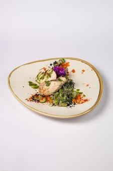 Filetto di pollo alla griglia al centro con mozzarella e pomodorini, su un cuscino di fagiolini e spinaci in crema su una superficie bianca
