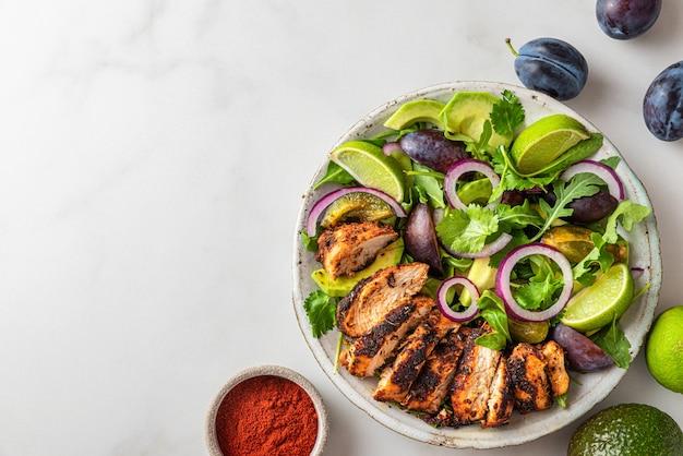 Insalata di filetto di pollo alla griglia con rucola, avocado, prugne, paprica, cipolla e lime in un piatto su sfondo bianco. vista dall'alto