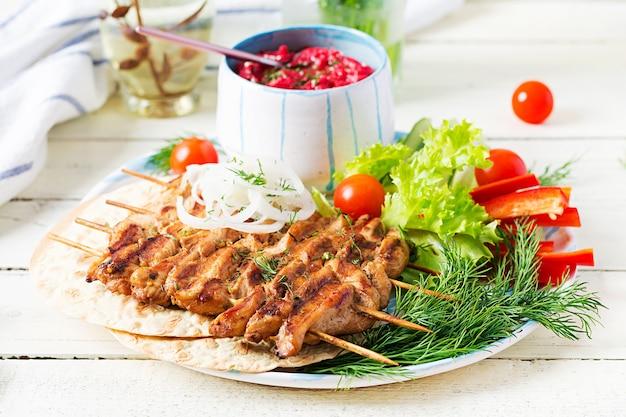 Spiedini di pollo alla griglia con hummus di barbabietola e pita, verdure fresche su un tavolo bianco