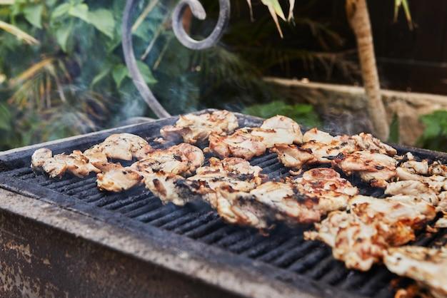 Cosce di pollo alla griglia con fumo di brace. festa barbecue.
