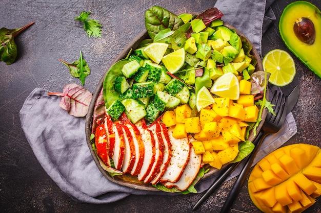 Pollo alla griglia, insalata di mango e avocado in un piatto scuro su sfondo scuro, vista dall'alto.