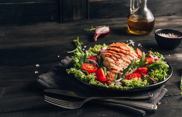 Pollo alla griglia e insalata sul tavolo