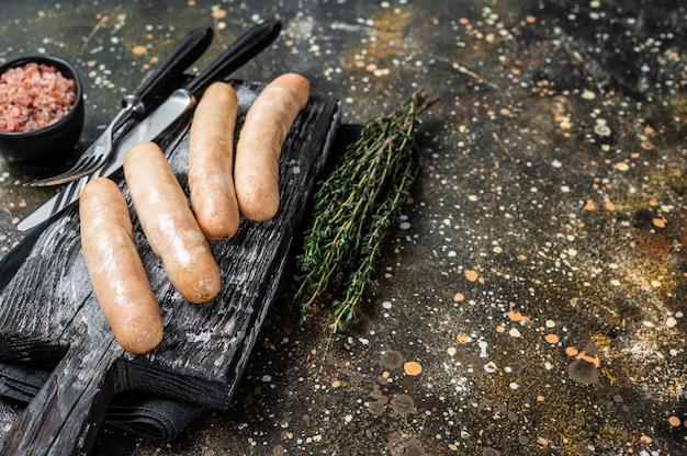 Salsicce di pollo alla griglia su una tavola di legno. sfondo marrone. vista dall'alto. copia spazio.