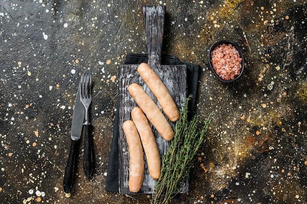Salsicce di pollo alla griglia su una tavola di legno. sfondo marrone. vista dall'alto.