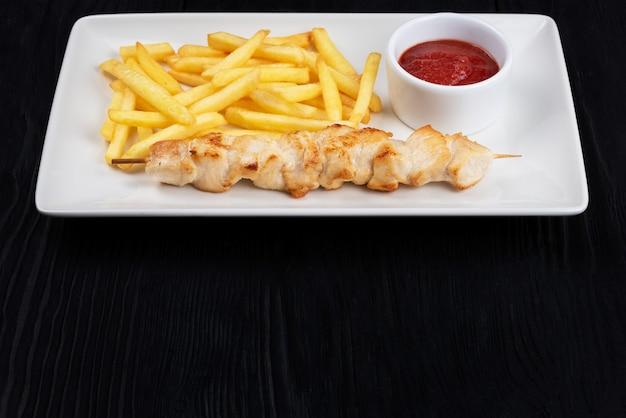 Carne di spiedini di pollo alla griglia con patate fritte su piatto bianco su fondo di legno nero