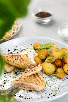 Bistecca di pollo alla griglia con patate idaho su piatto in ceramica con ingredienti su tavola di cemento.