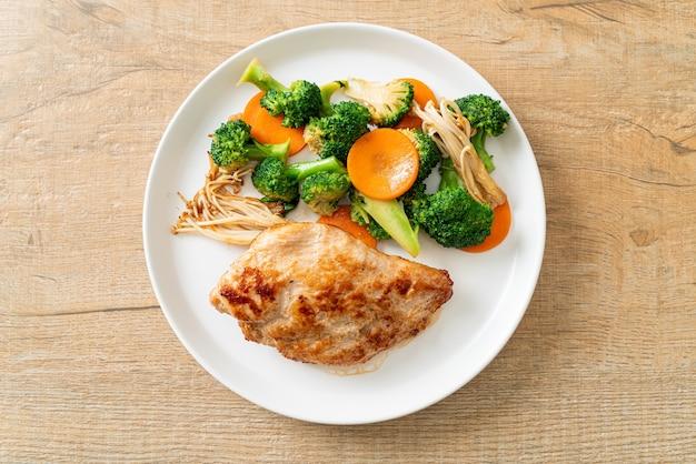 Bistecca di pollo alla griglia con verdure su piatto bianco