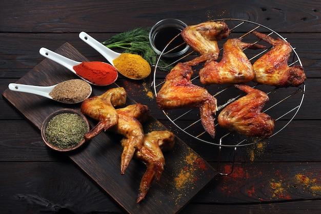 Ali di pollo alla griglia e spezie su un tavolo di legno