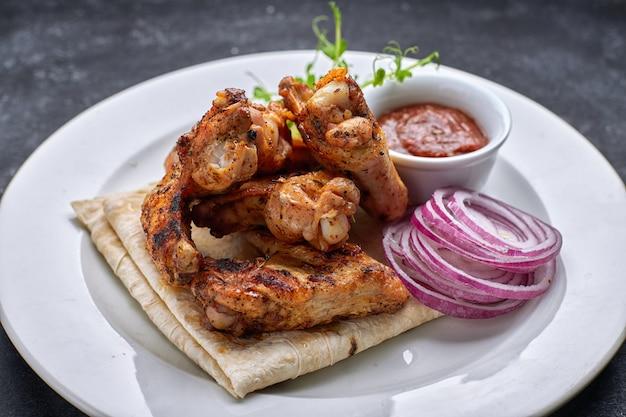 Ali di pollo alla griglia con salsa barbecue, pane pita, microgreen e anelli di cipolla, su un piatto bianco, contro un tavolo scuro