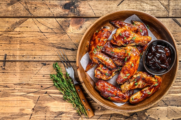Ali di pollo alla griglia con salsa barbecue. tavolo di legno. vista dall'alto. copia spazio.