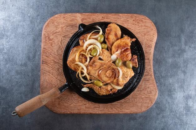 Pollo alla griglia con cipolle e olive su vista dall'alto piastra di ferro.