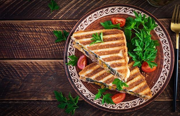 Club sandwich panini alla griglia con carne di manzo, pomodoro, formaggio e senape in foglia. deliziosa colazione o spuntino. vista dall'alto, copia spazio, sovraccarico