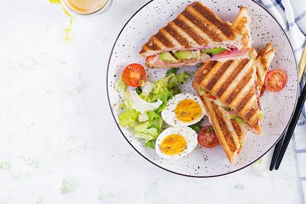Panini alla griglia club sandwich con prosciutto, pomodoro, formaggio, avocado e tazza di caffè