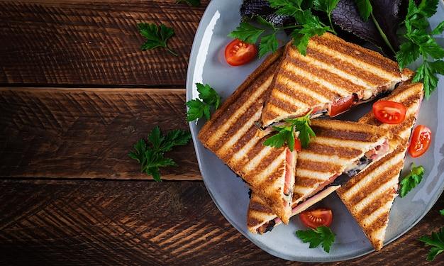 Panini club sandwich alla griglia con prosciutto, pomodoro, formaggio e senape in foglia. deliziosa colazione o spuntino. vista dall'alto, copia spazio, sovraccarico