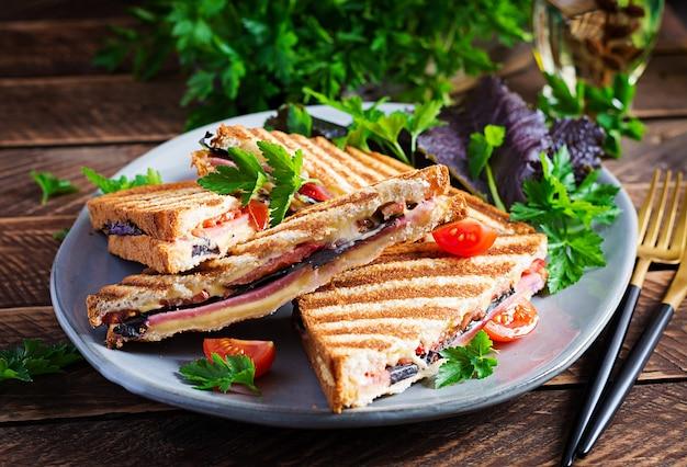 Panini club sandwich alla griglia con prosciutto, pomodoro, formaggio e senape in foglia. deliziosa colazione o spuntino.