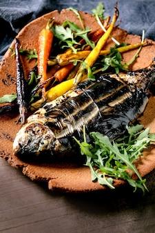 Pesce orata o dorado fresco cotto alla griglia su piatto di ceramica avvolto in foglie di bambù servito con erbe, carote colorate, tovagliolo blu su superficie marrone scuro. avvicinamento