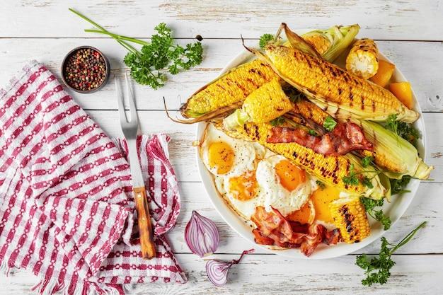 Mais alla griglia in pannocchie con uova fritte e fette di pancetta su un piatto bianco su un vecchio tavolo rustico con tovagliolo e forchetta, vista orizzontale dall'alto, piatto, close-up