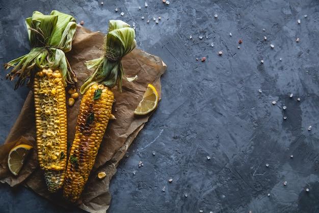 Pannocchie di mais alla griglia con salsa, coriande su sfondo di legno vecchio. cibo messicano. vista dall'alto. copia spazio, cibo sano, verdure