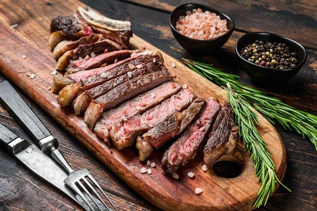Bistecca di manzo alla griglia da cowboy o rib eye con erbe e spezie. di legno. .