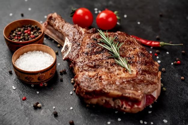 Bistecca di cowboy alla griglia con spezie su un coltello su un tavolo di pietra