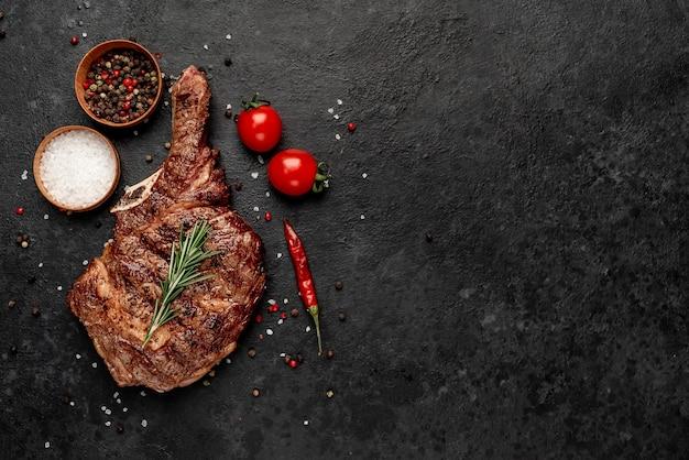Bistecca di cowboy alla griglia con spezie sul tavolo di pietra