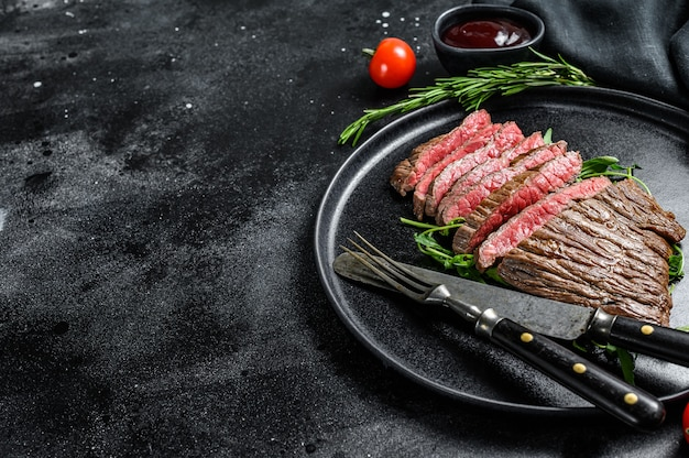 Bistecca di fianco alla griglia e tagliata. carne di manzo marmorizzata. sfondo nero. vista dall'alto. copia spazio.