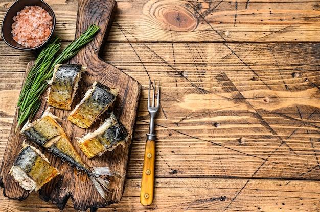 Pesce sgombro tagliato alla griglia sul tagliere. fondo in legno. vista dall'alto. copia spazio.