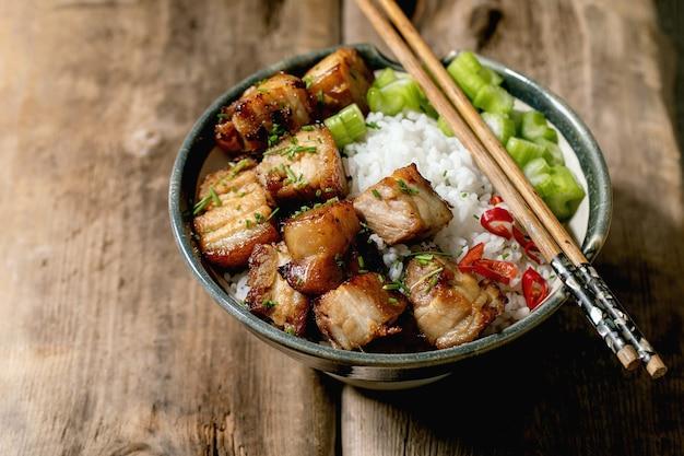 Pancia di maiale fritta profonda alla griglia nella ciotola con riso, sedano, peperoncino e cipollotto con le bacchette sopra fondo di legno vecchio.