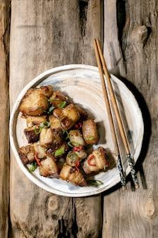 Pancia di maiale fritta profonda alla griglia con peperoncino e cipollotto sul piatto in ceramica con le bacchette sopra fondo di legno vecchio. lay piatto, copia dello spazio