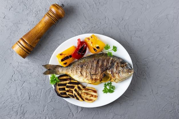 Pesce dorado alla griglia con verdure su fondo scuro