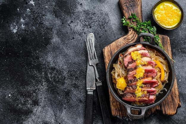 Bistecca di filetto di petto di anatra alla griglia con pasta e salsa di mandarini. vista dall'alto.