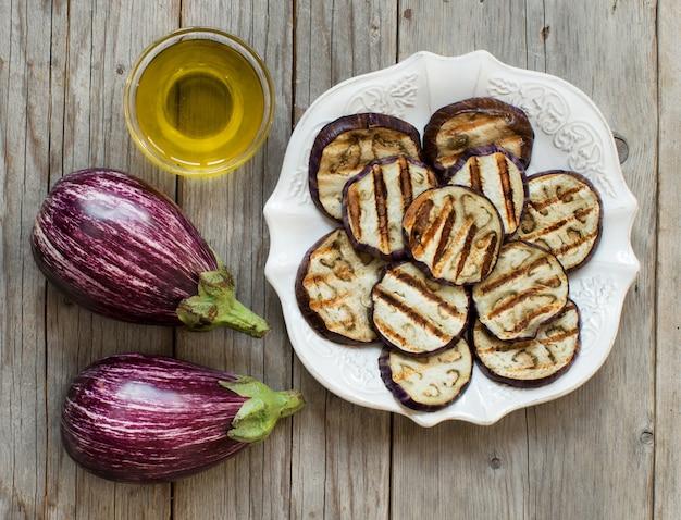 Melanzane grigliate condite con olio d'oliva sul tavolo in legno vista dall'alto