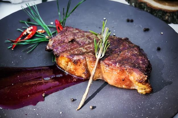 Filetto di manzo alla griglia condita con ramoscello di abete rosso salsa di pomodoro sul piatto. bistecca cotta alla siberiana