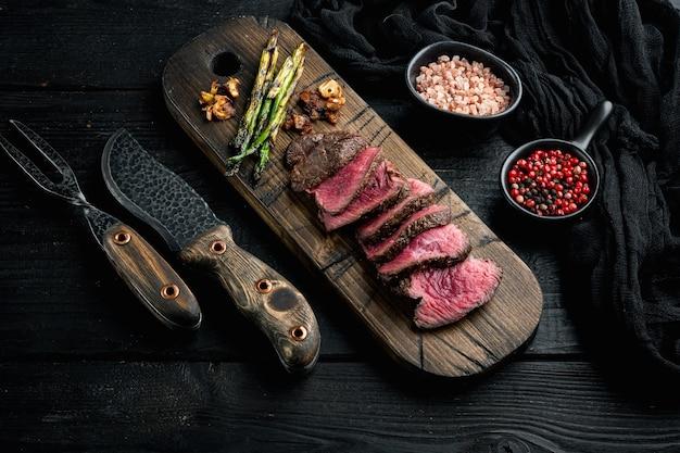 Set di bistecca di manzo mignon di filetto alla griglia, con cipolla e asparagi, su tagliere di legno, con coltello e forchetta per carne, su tavolo di legno nero