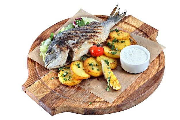 Dorado di pesce alla griglia sul bordo di legno rotondo isolato.