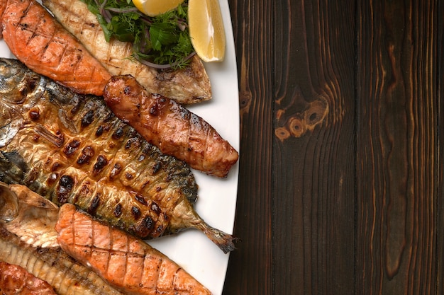 Pesce alla griglia su un piatto bianco con erbe e limone