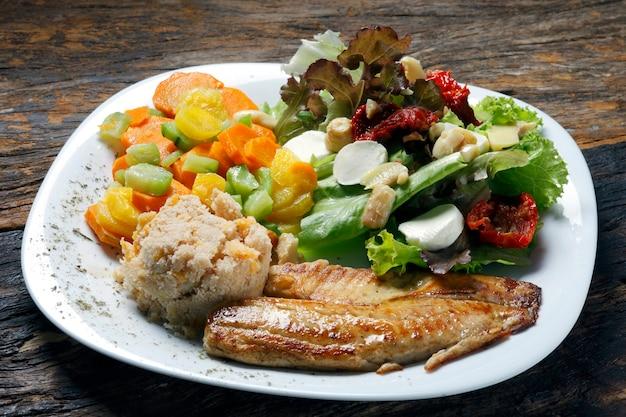 Pesce alla griglia con verdure e insalata