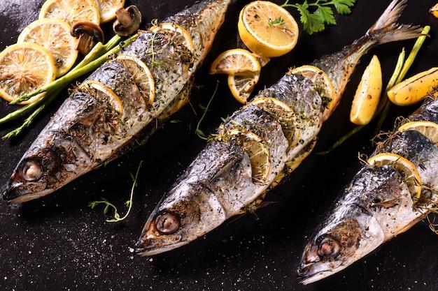 Pesci grigliati e verdure varie su piastra di ferro