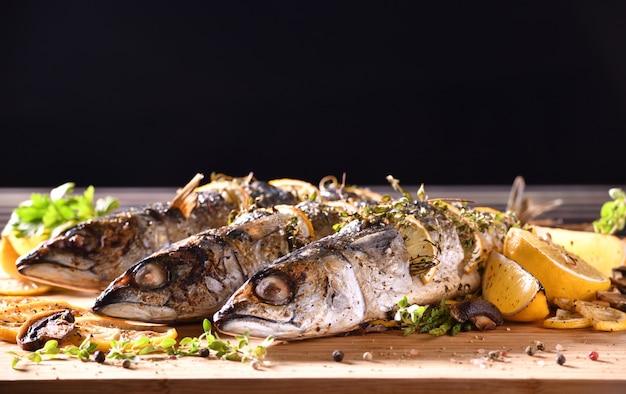 Pesci arrostiti e varie verdure sulla tavola di legno
