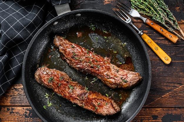 Bistecca di fianco alla griglia in padella. fondo in legno scuro. vista dall'alto.