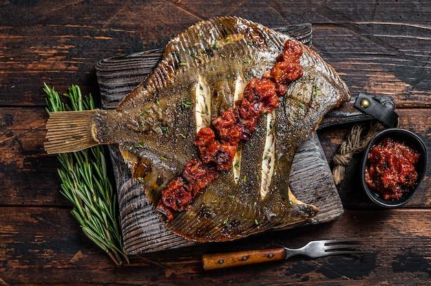 Passera di mare o passera di mare alla griglia con salsa di pomodoro sul tagliere di legno. tavolo in legno scuro. vista dall'alto.