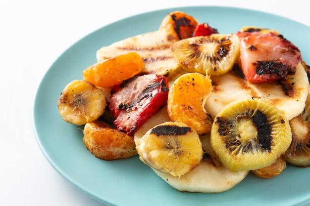 Frutta grigliata su un piatto blu isolato su priorità bassa bianca