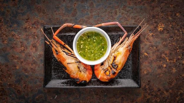 Gamberi d'acqua dolce giganti alla griglia con salsa di immersione di pesce piccante tailandese in piatto di ceramica rettangolare nero su sfondo arrugginito, vista dall'alto, gamberi di fiume