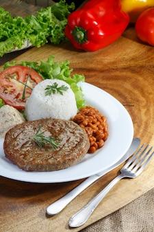 Hamburger di carne alla griglia con riso, fagioli e insalata