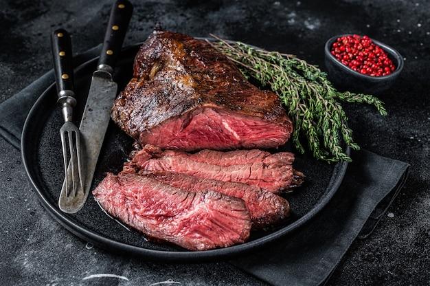 Gruccia alla griglia o bistecca di carne di manzo onglet su un piatto con timo. tavolo nero. vista dall'alto.