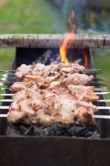 Kebab alla griglia che cucina su spiedino di metallo carne arrosto cotta al barbecue fette di braciola di carne di manzo fresca al barbecue piatto tradizionale orientale shish kebab griglia su carbone e fiamma picnic cibo di strada Foto Premium