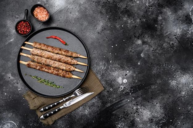 Set di kebab alla griglia, su piastra, su sfondo di tavolo in pietra scura nera, vista dall'alto piatta, con spazio di copia per il testo