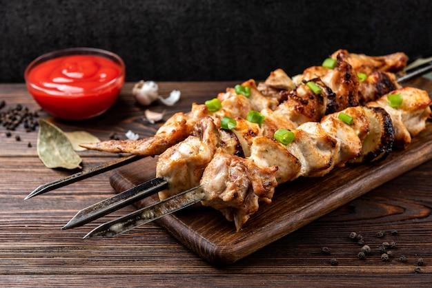 Kebab alla griglia con ketchup e spezie su fondo in legno.