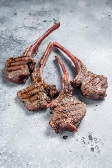 Bistecche di carne di montone di agnello alla griglia. sfondo grigio. vista dall'alto.